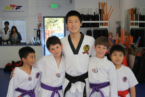 Johnny Lee ('15) poses with his taekwondo students at Palo Alto Martial Arts.